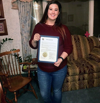 Schroeder '15 with signed petition from the mayor of Kearney, announcing National Adoption Day