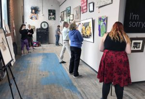 Students in a gallery hanging art for a show.