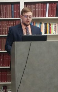 Photo of Austin Heinlein giving a presentation at a podium.