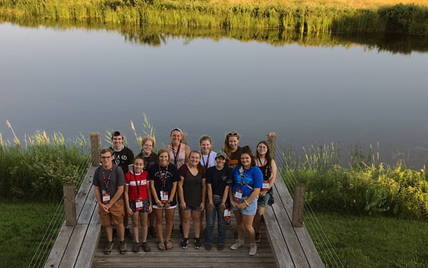 Students on a dock beside a river.