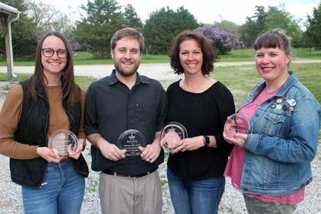 Picture of four individuals holding awards.