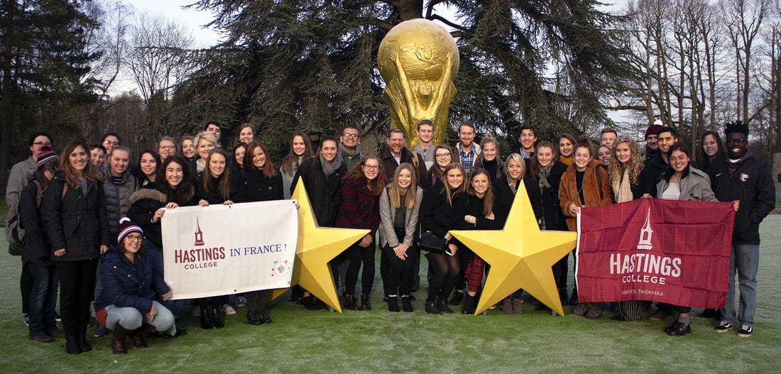 Students lined up for a photo outside a soccer complex in France.