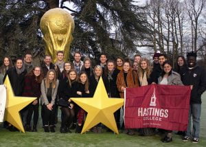 Students lined up on the lawn outside a soccer facility in France.