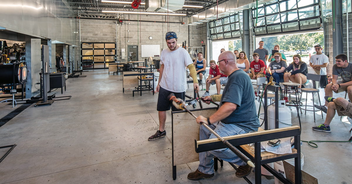 Photo of Tom Kreager and students in a glass studio.