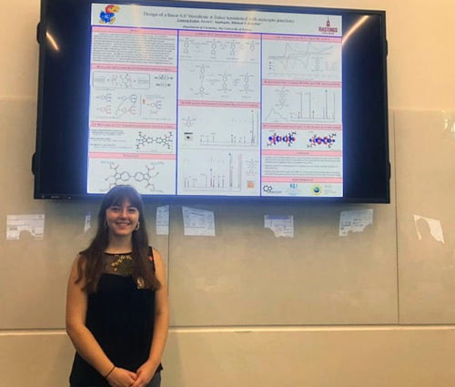 Student in front of a scientific poster