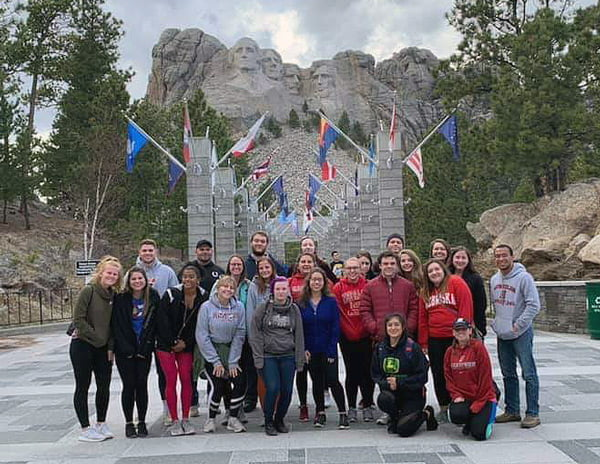 Students pose for a picture in front of Mount Rushmore.