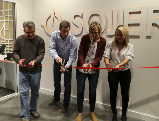 Brent Brummer '04 (second from left) cutting the ribbon in August at Sojern's new headquarters.