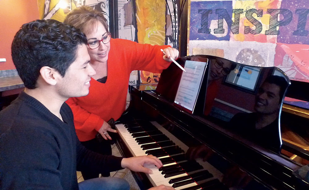 Dr. Hillary Watter working with a student at a piano.