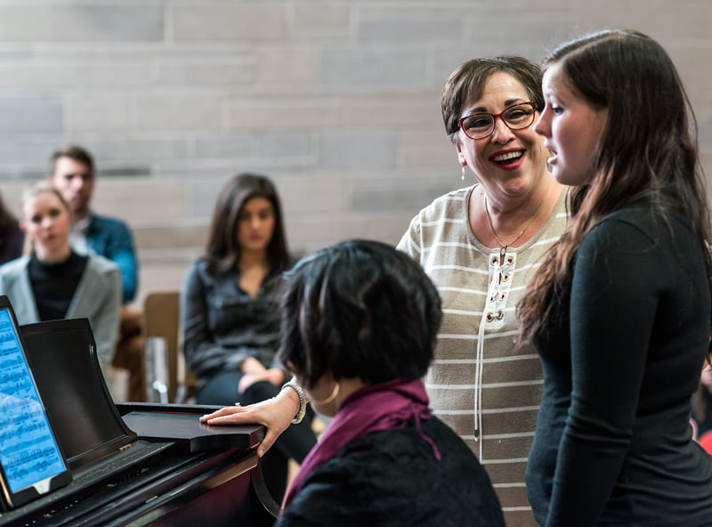 Dr. Hillary Watter working with a student who is singing.