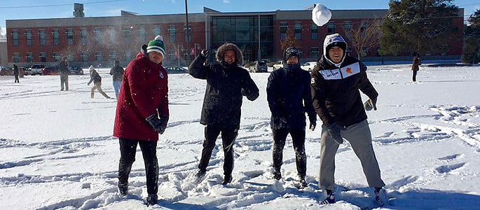 Students throwing snowballs in the winter