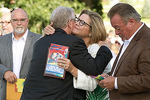 A photo of President Don Jackson greeting Kim and Tom Dinsdale.