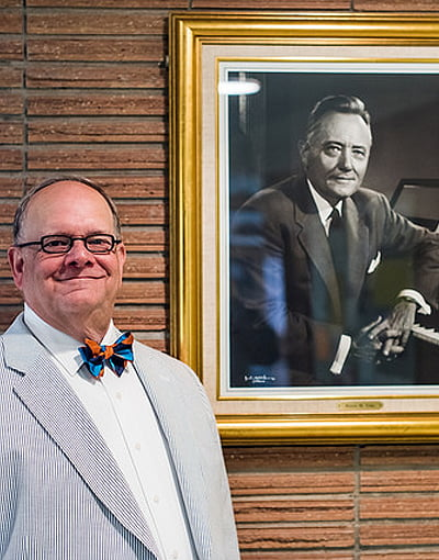 Photo of Robin Koozer standing next to a framed portrait of Hayes M. Fuhr.